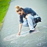 Girl draws a chalk. The girl draws a chalk on asphalt royalty free stock images