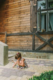 Girl draws a chalk near a wooden house Royalty Free Stock Photography