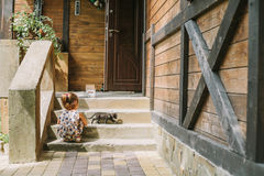 Girl draws a chalk near a wooden house.  stock images