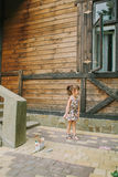 Girl draws a chalk near a wooden house Stock Photos