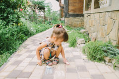Girl draws a chalk near a wooden house Stock Image