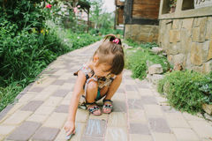 Girl draws a chalk near a wooden house Royalty Free Stock Photo
