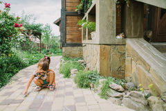 Girl draws a chalk near a wooden house.  stock photos