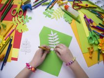 Girl draws. Children`s creativity. Favorite hobby for children. Materials and tools. Small child makes paper crafts for mother`s day or birthday. Small child Stock Photography
