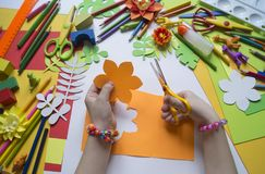 Girl draws. Children`s creativity. Favorite hobby for children. Materials and tools. Small child makes paper crafts for mother`s day or birthday. Small child Royalty Free Stock Photo