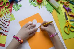 Girl draws. Children`s creativity. Favorite hobby for children. Materials and tools. Small child makes paper crafts for mother`s day or birthday. Small child Stock Image