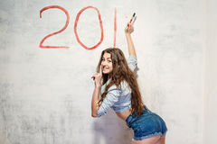 Girl draws a Christmas decoration on the wall. Girl in jeans shorts and jacket draws a Christmas (new year) decoration on old white wall with the red paint Royalty Free Stock Photo