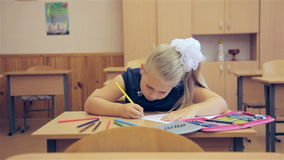 The girl draws in the classroom stock footage