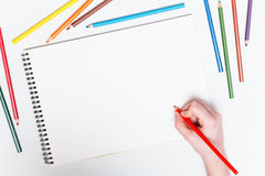 Girl draws with colored pencils on paper. Mockup stock images