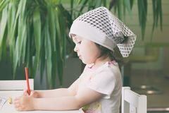 The girl draws in colored pencils. Side view royalty free stock photography
