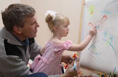 Girl draws a cow. Little girl draws colour felt-tip pens a cow Royalty Free Stock Photography