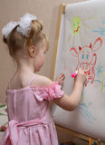Girl draws a cow. Little girl draws colour felt-tip pens a cow Royalty Free Stock Photo