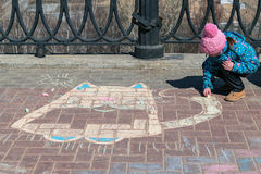 The girl draws with crayons cat on the pavement. Little girl in hat and jacket draws with colored chalk the fat cat on the pavement. On the street a Sunny Stock Image
