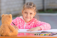 Girl draws with crayons and smile, he looked Royalty Free Stock Image