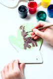 Girl draws deer paints on wooden mitten. Christmas gift. Royalty Free Stock Photo