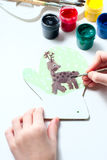 Girl draws deer paints on wooden mitten. Christmas gift. Stock Images