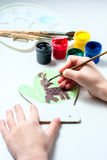 Girl draws deer paints on wooden mitten. Christmas gift. Royalty Free Stock Photos
