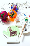 Girl draws deer paints on wooden mitten. Christmas gift. Stock Photos