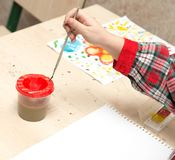 A girl draws a drawing with paints on a sheet.  Stock Photos