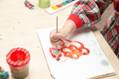 A girl draws a drawing with paints on a sheet.  Stock Photography