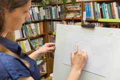 The girl draws on the easel in library. The girl draws on the easel in the library stock photos