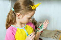 The girl draws a face with watercolors on her palm. Royalty Free Stock Image