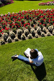 Girl draws flowers. A young girl sits on the grass and sketches a flower from a flower garden Royalty Free Stock Photo