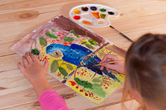 Girl draws gouache. Girl draws a large parrot gouache on paper in warm colors Stock Photography