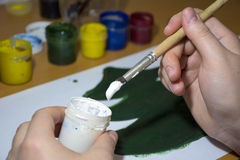 The girl draws green, white paint and brush Christmas tree Royalty Free Stock Image