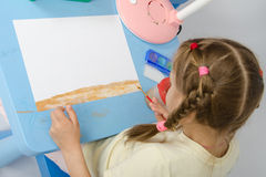 Girl draws on the ground below Royalty Free Stock Photography