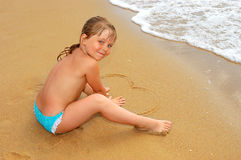 The girl draws heart on sand Stock Photography