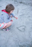 The girl draws heart on sand. Royalty Free Stock Images