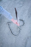The girl draws heart on sand. Royalty Free Stock Image