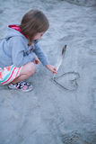 The girl draws heart on sand. Stock Images
