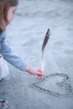 The girl draws heart on sand. Stock Photography