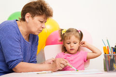 A girl draws with her grandmother Stock Photo