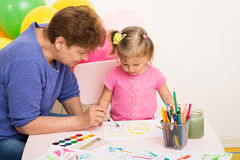A girl draws with her grandmother Stock Photography