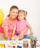 A girl draws with her mother Stock Photos