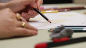 Girl draws left-handed with colored pencil on paper, detailed view in slowmotion. Girl draws left-handed with colored pencil on paper, detailed view in 2x stock footage
