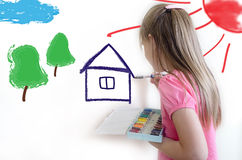 The girl draws on a light wall Royalty Free Stock Photography