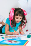 The girl draws lying on a floor Royalty Free Stock Photo