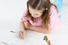 Girl draws lying on the floor Stock Photography
