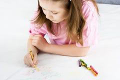 Girl draws lying on the floor Stock Image