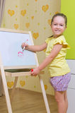 Girl draws a marker on white board Royalty Free Stock Photography