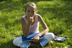 The girl draws on a meadow III. The nice girl draw on a meadow Royalty Free Stock Photography