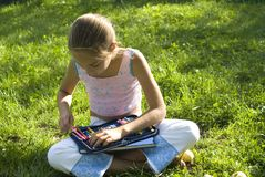 The girl draws on a meadow IV. The nice girl draw on a meadow Stock Photo