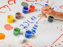 The girl draws messy signs on a wooden table. royalty free stock photos