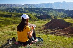 Girl draws on nature spring landscape. Painting outdoors. Kazakh. Stan. Mountain landscape stock photography