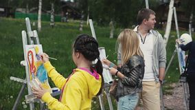 Girl draws painting on easel in green park on summer festival among other people stock footage