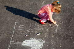 Girl draws painting line a chalk on asphalt. Girl sits on concrete asphalt square road. girl draws painting line a chalk on asphalt. chld drawings paintings on royalty free stock photos